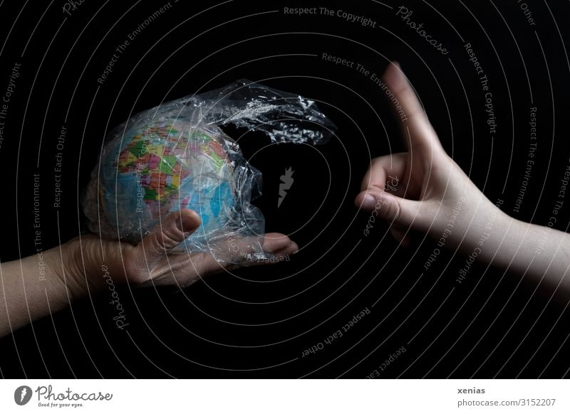 Not like that! Hand holding earth globe with plastic wrapped negative forefinger Earth no Environmental pollution Globe Plastic waste by hand Fingers Nature