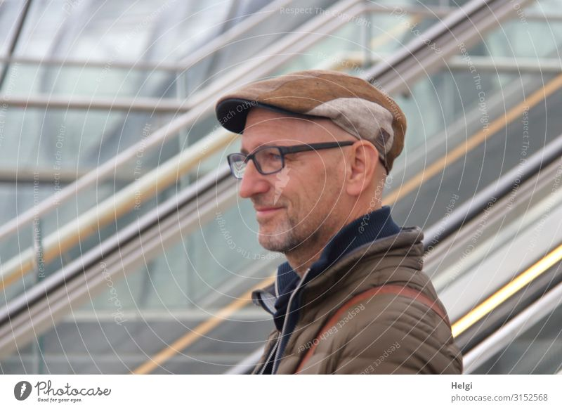 Portrait of a friendly smiling man with beard, glasses and cap Human being Masculine Man Adults 1 45 - 60 years Escalator Clothing Jacket Eyeglasses Hat