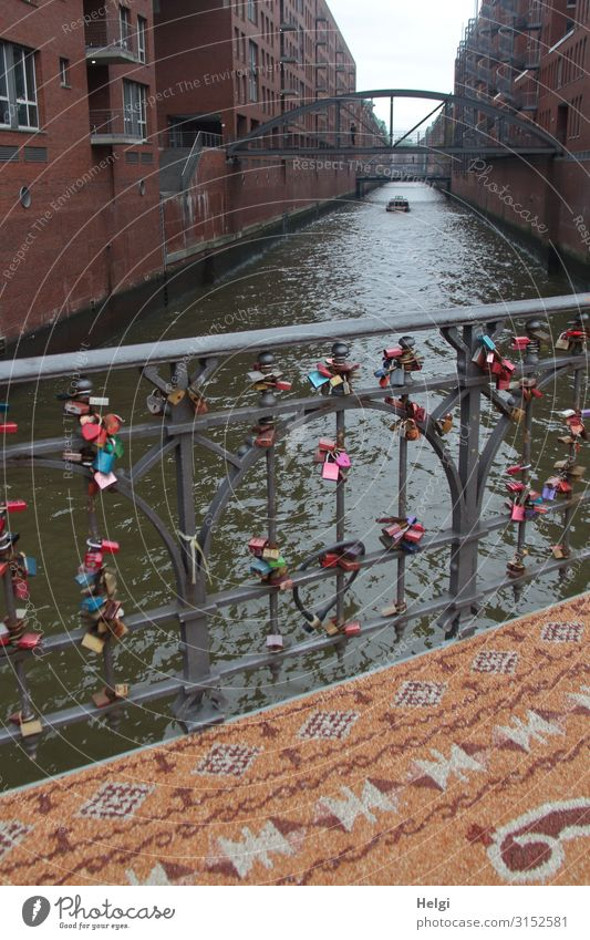 Bridge railing with many love palaces, in front of it a patterned carpet of small stones in the Speicherstadt Hamburg Water Port City Building Architecture