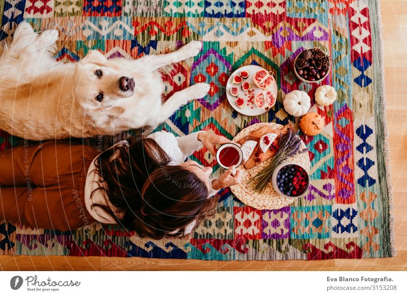 beautiful woman and cute golden retriever dog enjoying healthy breakfast at home, lying on the floor. healthy breakfast with tea, fruits and sweets. top view