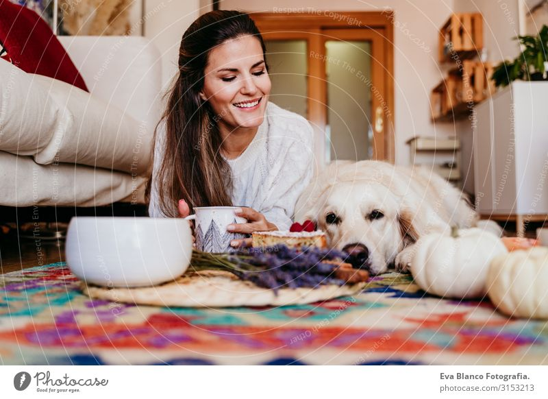 beautiful woman and cute golden retriever dog enjoying healthy breakfast at home, lying on the floor. healthy breakfast with tea, fruits and sweets. autumn season