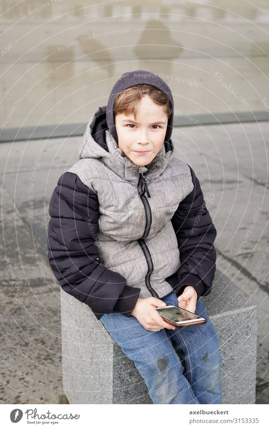 Boy with Smartphone Lifestyle Leisure and hobbies Playing Winter Child School Schoolyard Telephone Cellphone PDA Technology Internet Human being Boy (child)