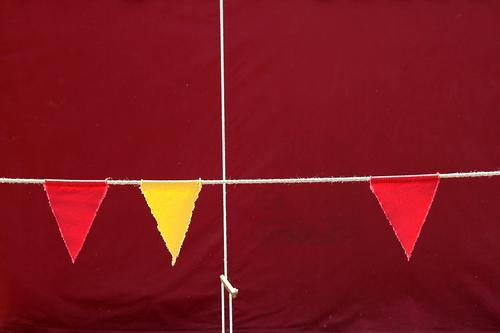 Tensioned rope, cord as a cross, in front of a tarpaulin made of fabric from a tent, at an event with flags, pennants in red and yellow, against a background in wine red, Bordeaux.