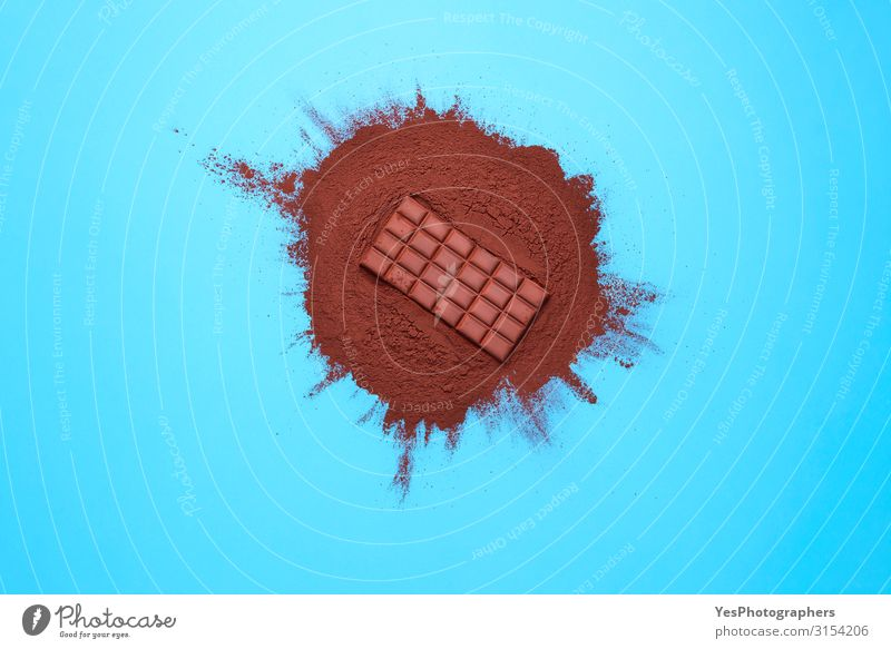 Chocolate bar on cocoa powder pile. Chocolate and ingredients Food Dessert Candy Brown Tradition Christmas cooking above view background Blue background