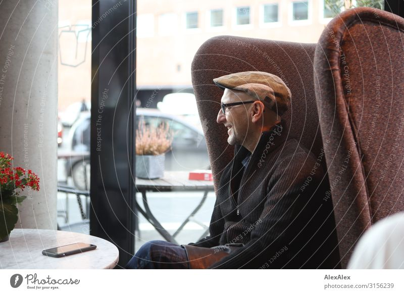 HH UT 19 Man sitting in Ohrensessl, smiling in a cafe. Nutrition To have a coffee Adults 45 - 60 years Jacket Cap Eyeglasses Table Armchair Window