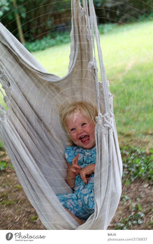 Little, sweet, blonde girl sits, lies happy and beaming in a hammock for children in the garden and laughs heartily into the camera. Leisure and hobbies Playing