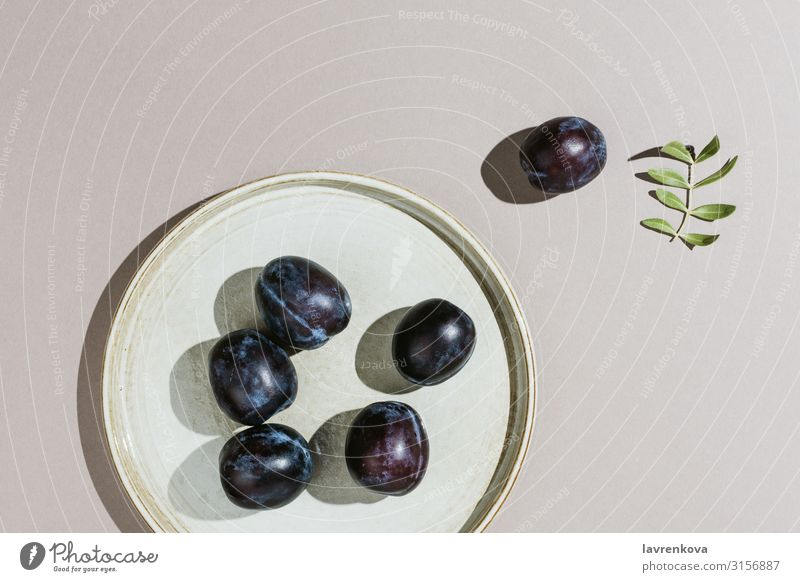Minimalist flatlay of plums on a handmade plate Diet Minimalistic Branch Leaf Plum Neutral Gray Juicy Nutrition Eating Summer Nature Raw Dessert Tasty Delicious
