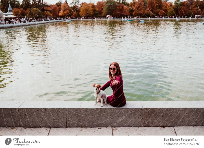 young woman and cute dog by the lake in an urban park. Love for animals concept. Retiro park Madrid Woman Dog Pet Lake Park Exterior shot City Embrace Together