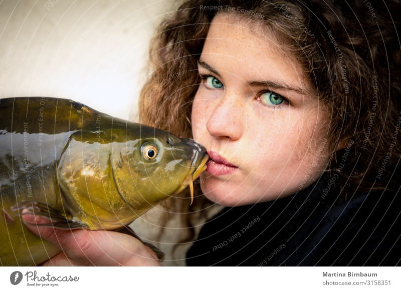 Young woman with impressive green eyesvkissing a carp, fish Seafood Dinner Lifestyle Happy Beautiful Face Fishing (Angle) Human being Feminine Woman Adults