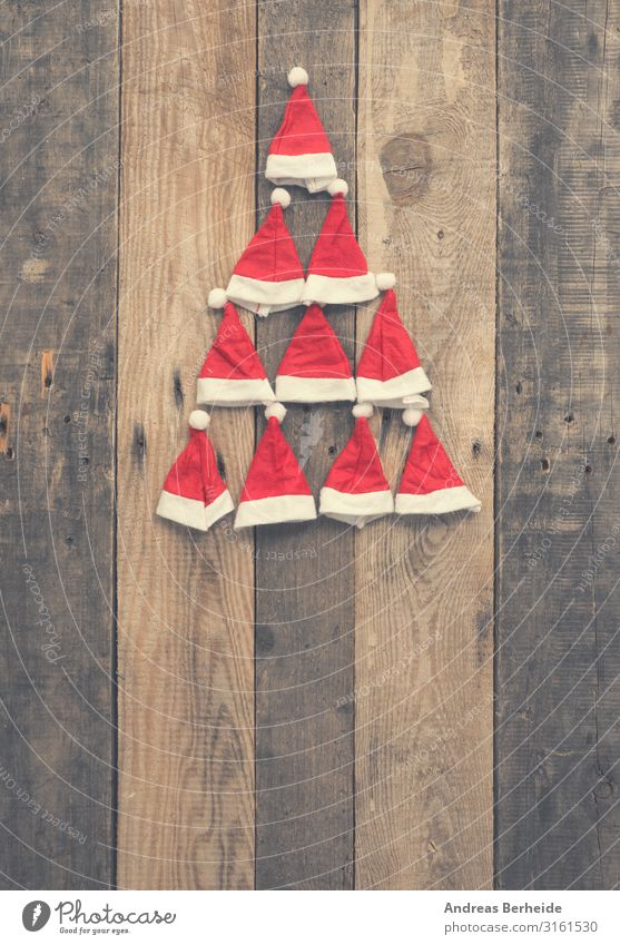 Christmas tree shape made with hats of Santa Style Winter Christmas & Advent Hat Cap Wood Ornament Tradition Santa Claus red rustic plank wooden nobody