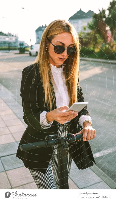 Businesswoman with e-scooter looking at cellphone Elegant Style Beautiful PDA Human being Woman Adults Transport Street Fashion Sunglasses Modern urban mobile