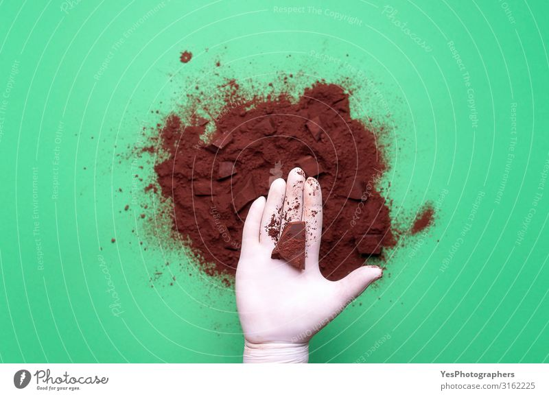 Chocolate chunk in hand and cocoa pile Chocolate piece and cacao Dessert Candy Hot Chocolate Hand Brown Tradition above view background cacao powder