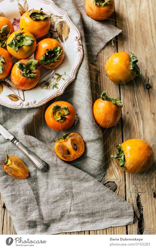 Tasty, ripe persimmons on a beautiful plate and wooden table sweet fresh tasty healthy dessert nutrition orange food raw tree fuyu vegetarian slice freshness