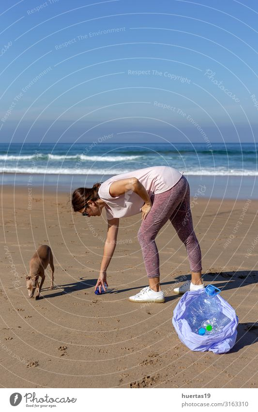 Woman with dog picking up trash and plastics cleaning the beach Human being Nature Dog Blue Water Landscape Hand Ocean Animal Beach Lifestyle Adults Environment