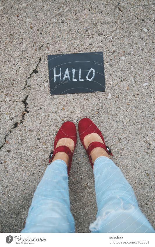 """Woman stands in front of a small board with the word """"hello"""" written on it . feminine Legs foot Footwear jeans Stand Street Asphalt Blackboard Written Chalk"""