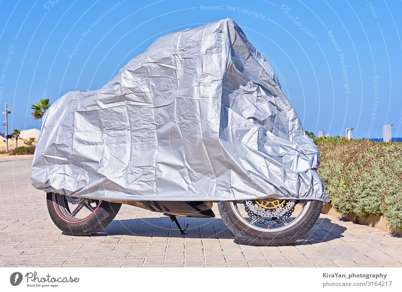 Waterproof cover for motorcycle with silver reflective protective surface. Motorcycle covered with fabric shield and parked outside Cover Blue Scooter Accessory