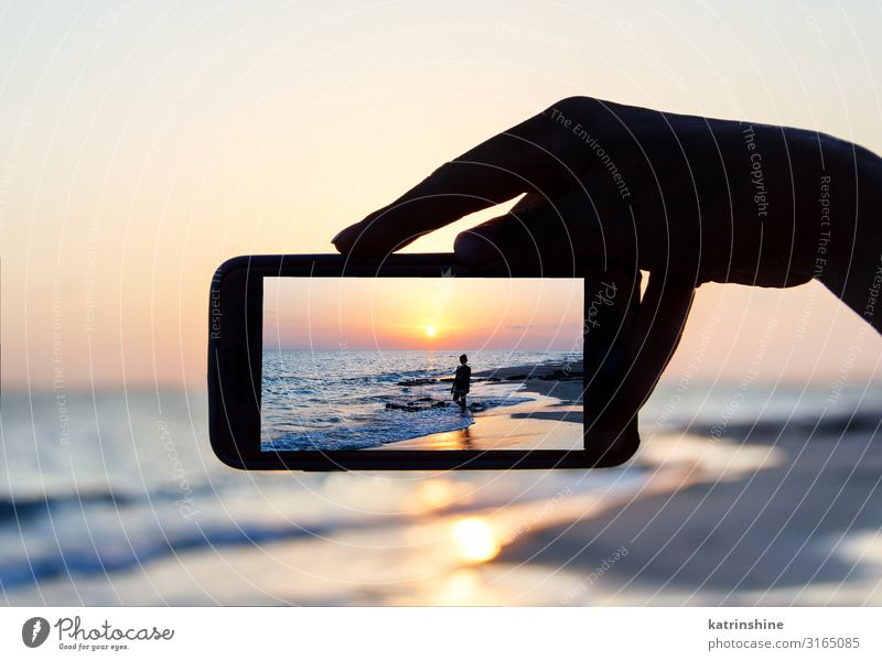 Man takes a sunset photo on the phone Vacation & Travel Summer Beach Ocean Cellphone PDA Technology Woman Adults Hand Environment Nature Landscape Sky Dark Blue