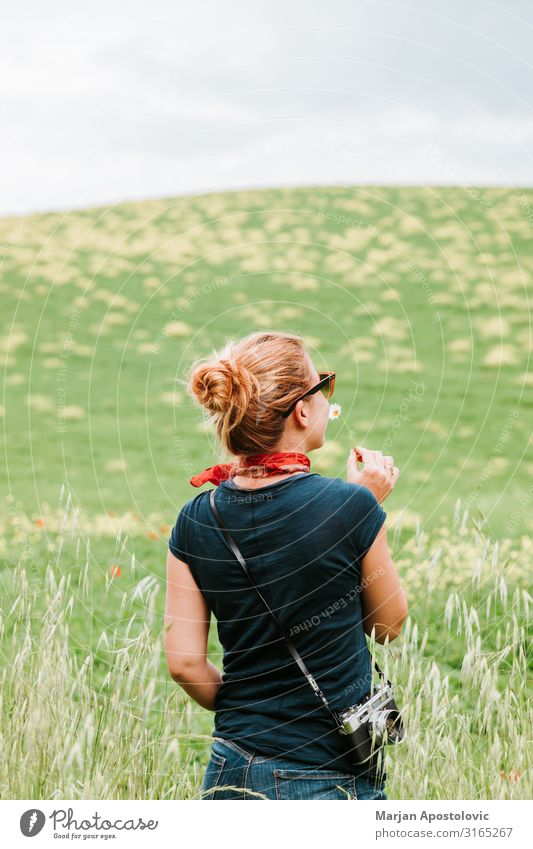 Young woman smelling flower in the field Lifestyle Joy Vacation & Travel Tourism Adventure Freedom Summer vacation Camera Human being Feminine