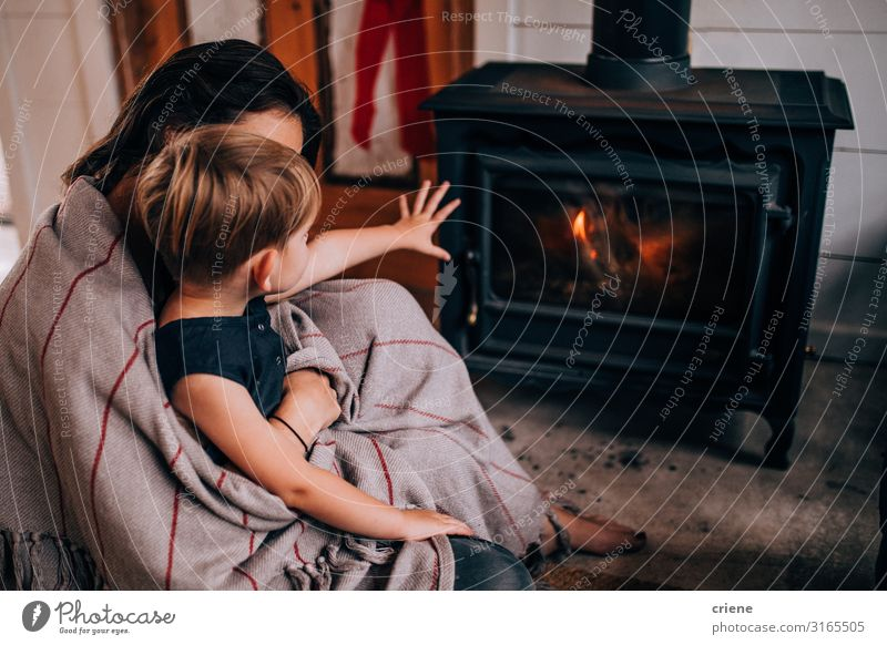 woman and toddler son sitting in front of fireplace Winter Mother Adults Family & Relations Warmth Hot Son wood flame burning Home heat stove interior room Log
