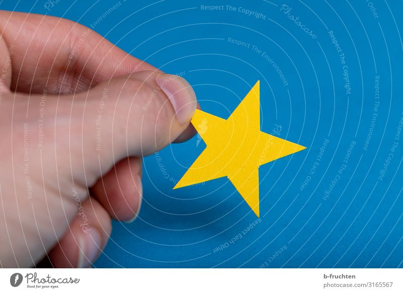 yellow star on blue background Office Economy Business Career Success Fingers Paper Decoration Sign Flag Work and employment Select Touch Movement To hold on