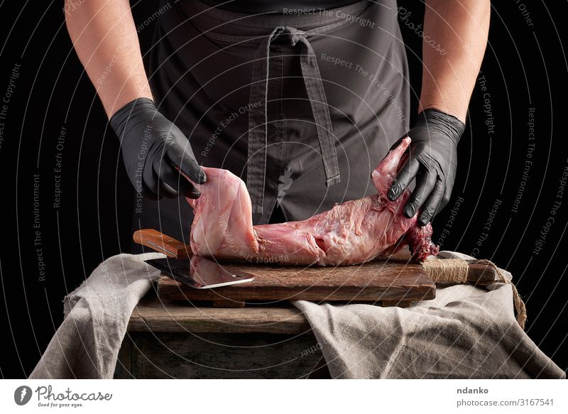 chef in black latex gloves holds a whole rabbit carcass Meat Nutrition Dinner Knives Table Kitchen Man Adults Hand Gloves Wood Eating Make Dark Fresh Red Black