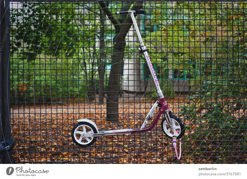 Connected scooter Parking lot Relaxation Keep Border Autumn Hang Kindergarten Wire netting fence Deserted Scooter School building Schoolyard Copy Space Fence