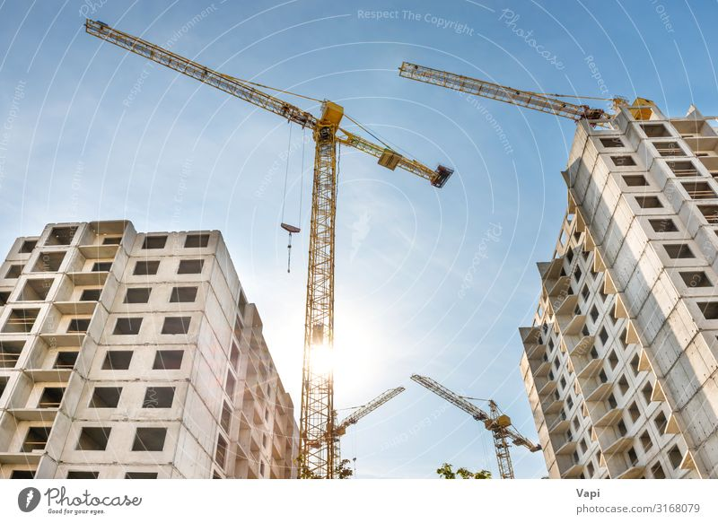 Construction site with cranes Sky Blue White Sun House (Residential Structure) Window Black Architecture Yellow Wall (building) Business Building Wall (barrier)