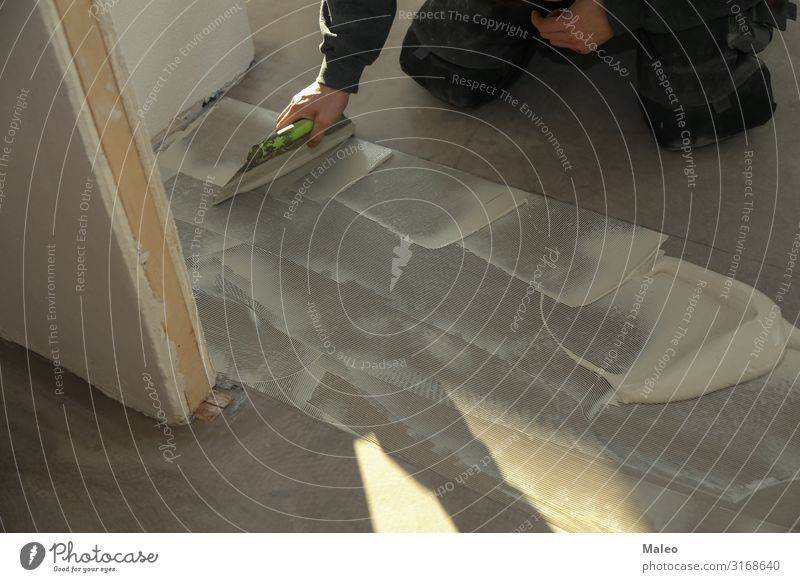 A worker installing new vinyl tile floor Man Construction site Repair House (Residential Structure) Flat (apartment) Floor covering Working man Tile Ground