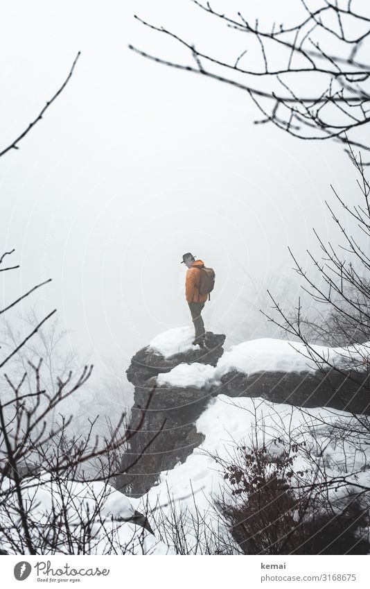 A man and a rock Lifestyle Well-being Contentment Senses Calm Leisure and hobbies Trip Adventure Freedom Winter Snow Winter vacation Hiking Human being
