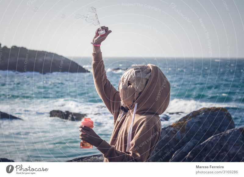 girl with mask blowing bubbles Lifestyle Leisure and hobbies Human being Child Girl Head Cap Mask Toys Stone Water Serene Colour photo Exterior shot Evening