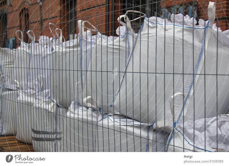 large filled white plastic bags stand on top of each other behind a building fence Hamburg Port City Wall (barrier) Wall (building) Sack Fence Stone Metal