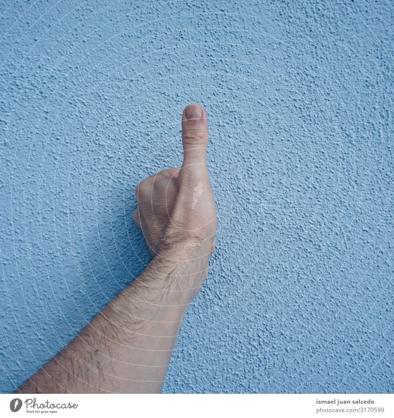hand gesturing ok on the blue wall Human being Blue Hand Street Wall (building) Body Skin Arm Fingers Symbols and metaphors Conceptual design Minimalistic