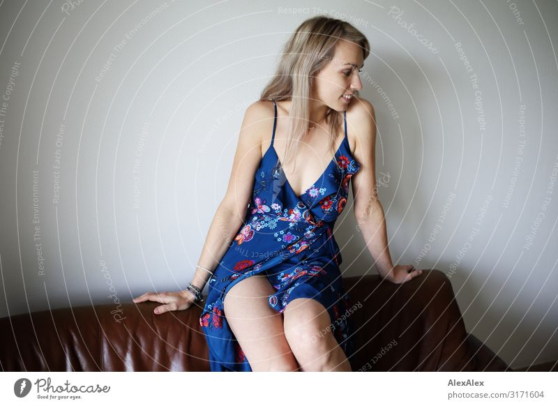 Woman sits on back of couch Style Joy Beautiful Harmonious Well-being Sofa Adults 30 - 45 years Dress Blonde Long-haired Smiling Sit Esthetic Authentic Happy