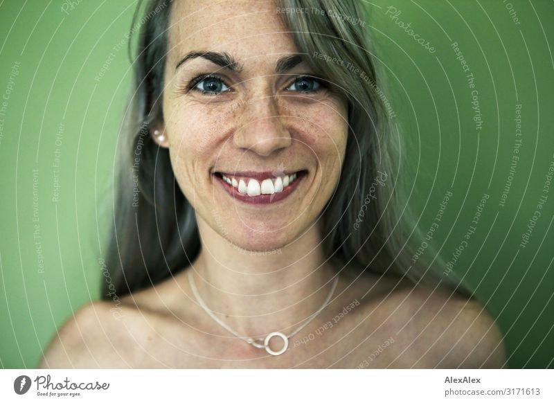 Portrait of smiling woman with freckles in front of green wall Style Joy pretty Life Harmonious Woman Adults Freckles 30 - 45 years Jewellery Blonde Long-haired