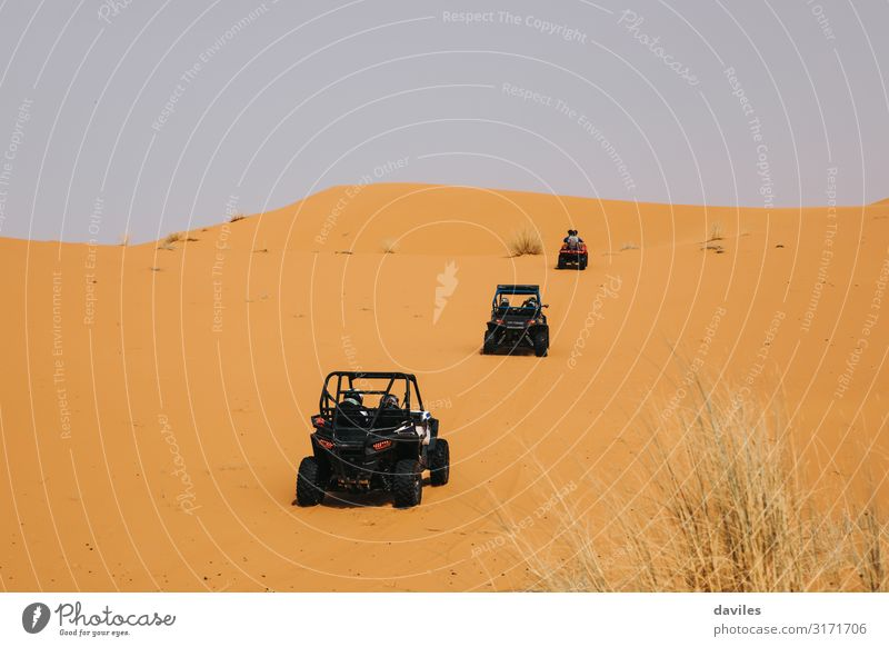 Rally buggies crossing dunes in the desert. Vacation & Travel Trip Adventure Safari Expedition Sports Motorsports Car race Engines Nature Landscape Sand Desert