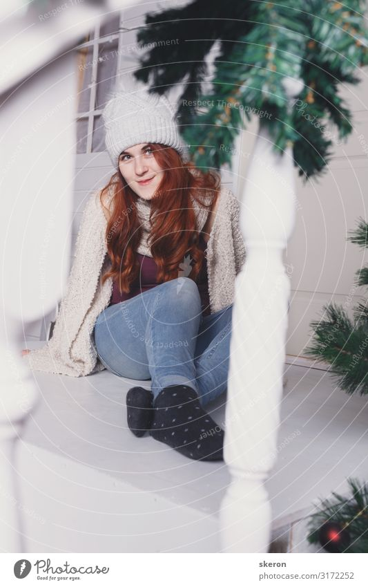 girl in a winter hat sits on the porch of a Christmas house Lifestyle Shopping Leisure and hobbies Entertainment Party Event Christmas & Advent New Year's Eve