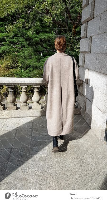 Rear view of a young woman in a long coat on an old balcony Young woman Coat Balcony Romeo and Juliet historical building Colour photo Exterior shot Building