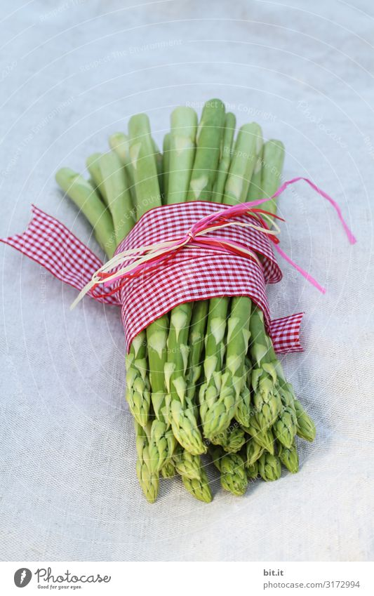 A portion of green asparagus, freshly harvested from the local field, lies on the table, decorated with a checkered ribbon of fabric, tied together, in the light, with a white linen cloth.