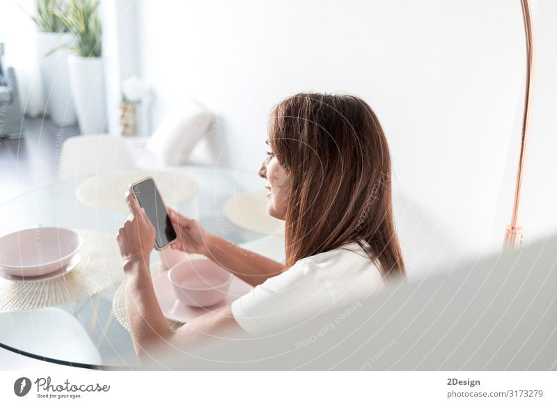 Rear view of adult woman using mobile phone Lifestyle Relaxation Playing Reading Flat (apartment) Sofa Living room Telephone Cellphone PDA Screen Human being