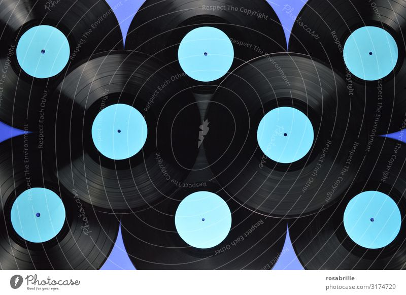 many old black vinyl records stacked on top of each other with empty turquoise label on blue background | symmetry Record LP Ancient Retro vintage Music Blue