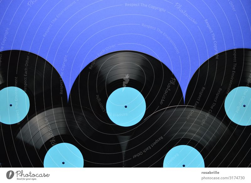 five old black vinyl records laid on top of each other with empty turquoise label on blue background as a band below with space for text above| symmetry Record