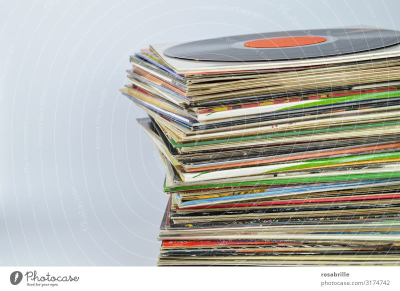 Stack of many old colorful vinyl record sleeves on top of each other with a black record on top with a neutral orange label in front of a white background with free space for text on the left | old