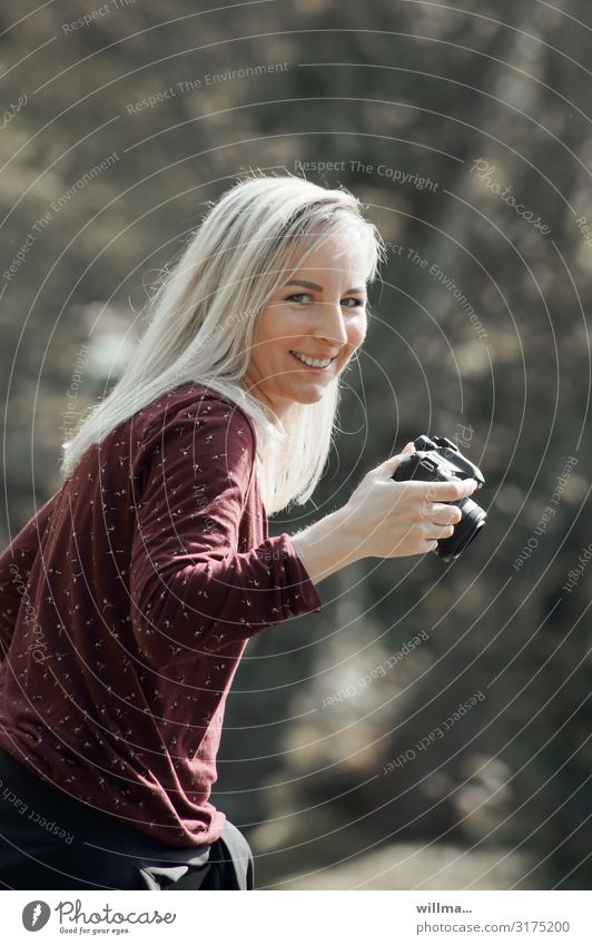 young blonde photographer with mischievous smile Young woman Woman Photographer Blonde Long-haired Laughter Friendliness Camera Smiling Funny Happiness Impish