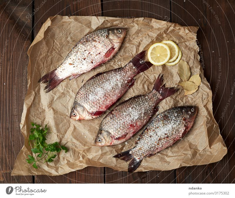 whole fresh crucian fish with scales Meat Fish Herbs and spices Nutrition Eating Dinner Diet Table Kitchen Animal River Paper Wood Fresh Delicious Natural Above