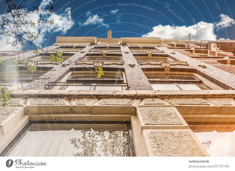 Stone Building Exterior Wall Details in Amsterdam Elegant Beautiful Sky Clouds Architecture Facade Old Tall Classic masonry window sunny directly below