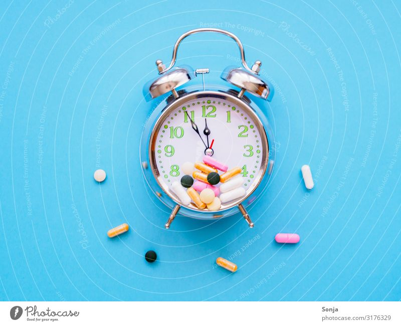 Alarm clock with colourful tablets on a blue background Lifestyle Healthy Health care Care of the elderly Clock hand Pill Blue background Sign