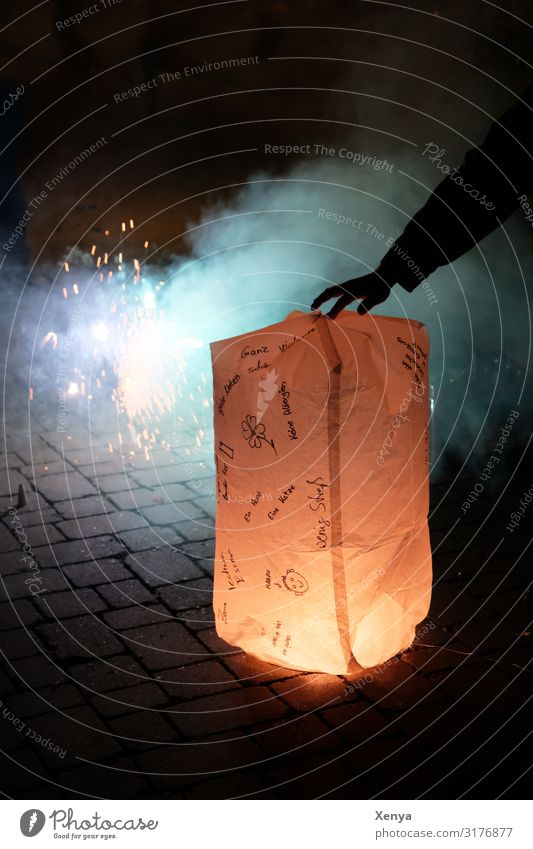Happiness in the New Year Masculine Arm Hand 1 Human being Winter Places Blue Brown Yellow Black White New Year's Eve Lampion sky lantern Chinese lantern