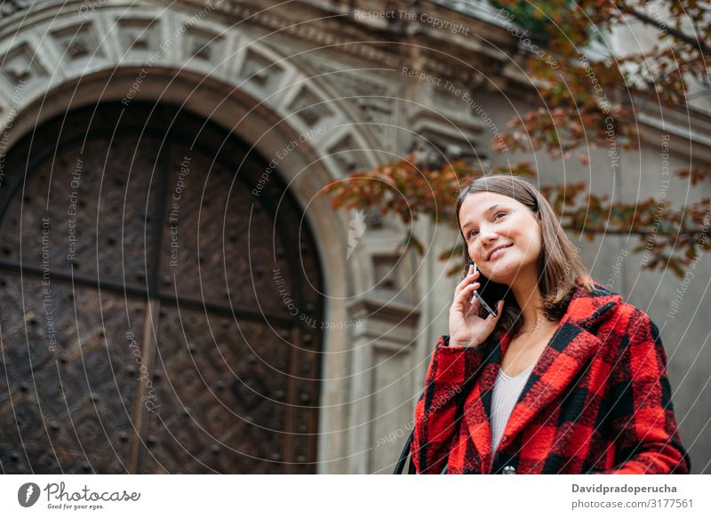 pretty young woman walking on the street using smartphone cell technology smile daylight looking away device gadget conversation outdoors city tail cheerful