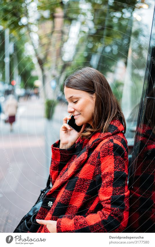 pretty young woman standing on glass on the street using smartphone cell technology smile daylight looking away device gadget conversation outdoors city tail