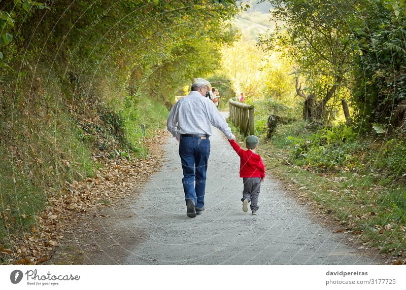 Grandfather and grandchild walking in nature path Lifestyle Joy Happy Leisure and hobbies Summer Child Baby Boy (child) Man Adults Parents Family & Relations